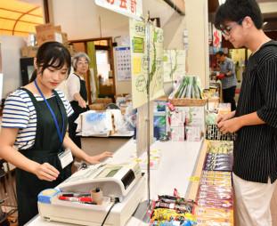 龍泉洞観光会館の売店で就業体験する佐々木理那さん(左)