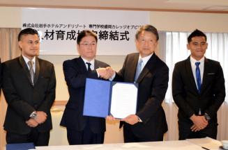 人材育成協定を締結し握手する山形明執行役員(左から2人目)と工藤昌雄校長