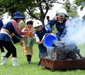 バケツリレーによる初期消火訓練に臨む参加者