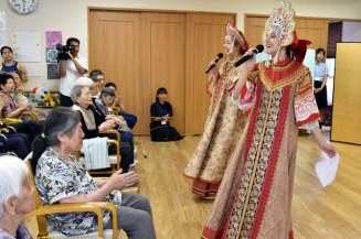 高齢者を前に、華やかな民族衣装で歌を披露するロシアの高校生