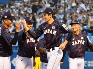 26日の壮行試合前に日本代表の仲間とハイタッチする佐々木朗希(右から2人目)。投手陣の柱として起用法にも注目が集まる=神宮