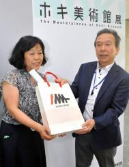 藁谷収館長(右)から入場2万人目の記念品を受け取る加藤孔子さん