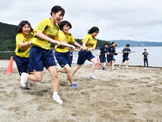 4人一組で棒を持ちながら、カラーコーンを回り進む競走で交流する山田高生(手前)と雫石高生