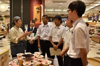 熟練した販売員から接客や陳列の手法を学ぶ宮古商高の生徒