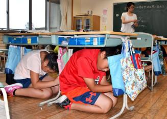 授業中の地震発生を想定し、机の下に潜り込む杜陵小児童