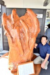 植野義水さん(右)が作製し、津軽石駅ホームに設置された巨大なサケの木彫り