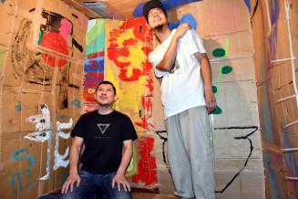 児童が制作したアート作品の中で絵を見つめる阿部宏司代表(左)と川村康徳店主