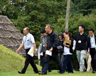 イコモスの現地調査を想定して御所野遺跡を案内する高田和徳館長(左)ら関係者