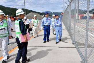 不審者の立ち入りを防ぐフェンスの破損がないかを確認する関係者