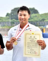男子カヤックシングル1000メートルで2連覇を果たし、メダルを手に笑顔を見せる水本圭治=3日、東京・海の森水上競技場