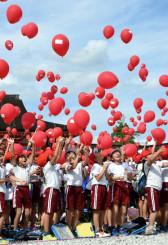 夢を書いた風船を一斉に空へ放つ子どもたち
