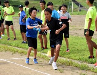 早稲田大競走部の指導を受け、ミニ駅伝でたすきをつなぐ子どもたち