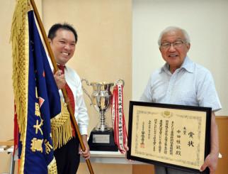 笑顔で大賞旗を手にする中田桂敏さん(左)と藤沢清美会長