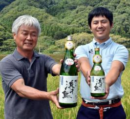 受賞作を手に喜び合う奥村康太郎さん(右)と佐々木重吾会長