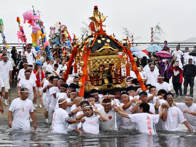 山田湾へ入水し、力強く進むみこしの担ぎ手たち=16日、山田町北浜町