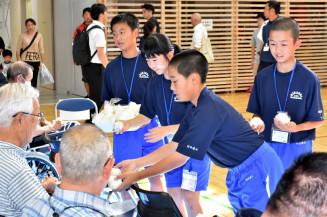 避難者に炊き出しで作ったおにぎりを配る釜石東中の生徒