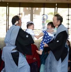 泣き相撲で対戦する子どもたち