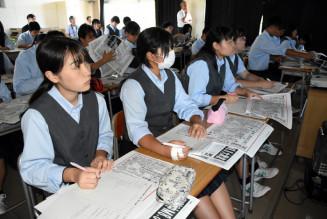 当時の岩手日報のコピーを手に明治、昭和、チリ地震の津波の説明を聞く山田高の1年生
