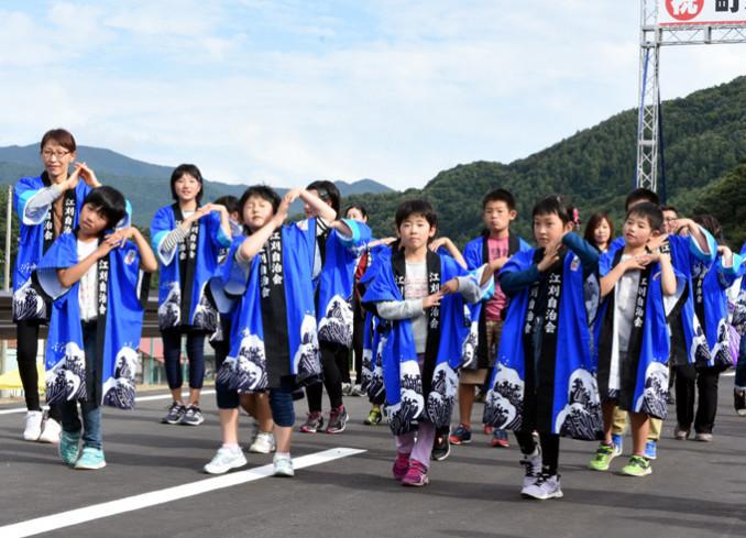 町道茶屋場田子線の開通を祝い、葛巻音頭を披露する子どもたち