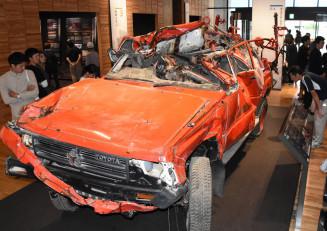 オープンした東日本大震災津波伝承館に展示された田野畑村消防団の被災車両。大勢の人がひしゃげた車体に見入り、津波の猛威を体感した=22日、陸前高田市気仙町