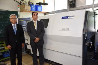 最新のCNC自動旋盤を贈った中島圭一社長(右)と三田章徳校長