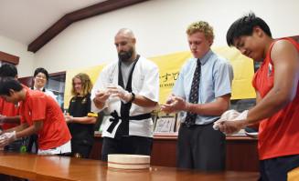 まぜご飯のおむすび作りに挑戦するスコット・ファーディーさん(右から3人目)や高校生ら