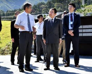 釜石祈りのパークで村上清館長(左)の説明を聞く田中和徳復興相(中央)