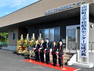 テープカットで給食センター完成を祝う佐藤信逸町長(右から3人目)ら
