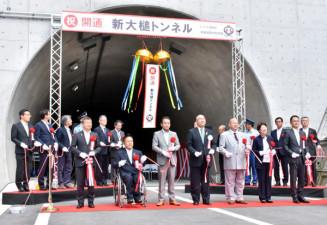 テープカットとくす玉割りで新大槌トンネル開通を祝う関係者ら