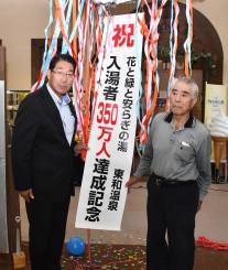 350万人達成を祝うくす玉を割る日下昭利さん(右)と佐々木力弥社長