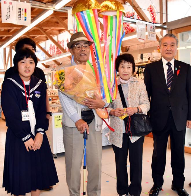 入館10万人目となった植竹正義さん、タカ子さん夫妻(中央)