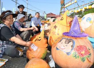 道路沿いに並ぶカボチャに飾り付けをする戸田地区の住民