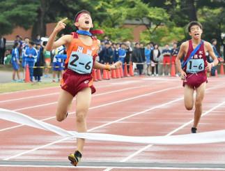 男子 アンカー勝負で競り勝ち、ガッツポーズでゴールする福岡の野崎太地(左)。右は西根の門屋佳一郎=花巻市・日居城野運動公園陸上競技場