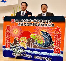 友好交流都市協定締結を記念した大漁旗を披露する山本正徳市長(右)と老松博行市長