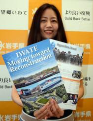 「国際イベントを機に多くの人に復興の現状を知ってほしい」と英語版の冊子を掲げる山谷佳子企画専門員
