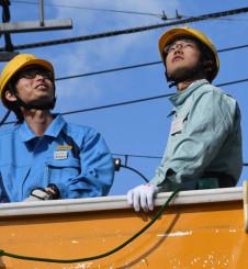 高所作業車に乗り、地上15メートルの高さを体験する生徒(右)