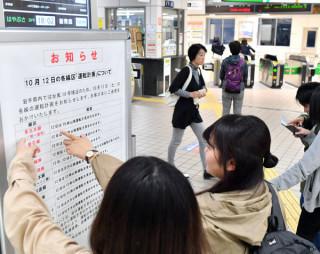台風19号の接近に伴い、列車の運休を知らせる看板を見る乗客。交通への影響が拡大した=11日、盛岡市・JR盛岡駅