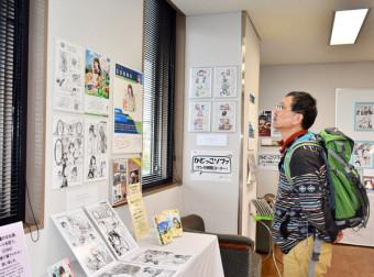 北上市出身の漫画家の作品を見入る来館者