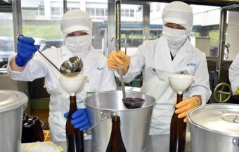ぶどうジュースの瓶詰め作業に取り組む生徒たち