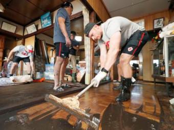 床上浸水した住宅から泥をかき出すラグビーW杯カナダ代表のピーター・ネルソン=13日午後、釜石市