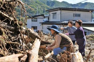 自宅に押し寄せた土石流に言葉を失う芦生ユキさん(左)=13日午後0時5分、普代村中心部