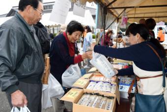 3市町の特産品が販売された特設ブースでうどんなどを購入する来場者
