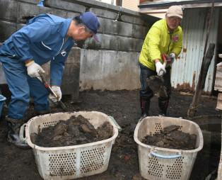 建物の周辺を埋め尽くした泥の除去作業に励むボランティア=普代村太田名部