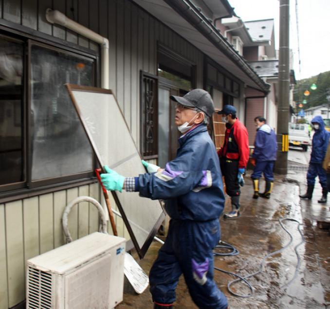 断続的に雨が降り続く中、浸水した自宅の復旧作業を急ぐ住民たち=19日午後3時12分、普代村普代