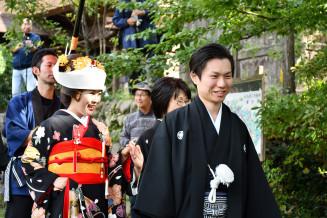 晴れやかな表情で「花嫁道中」に参加する藤田哲平さん(右)と千咲さん夫妻