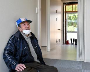 仮設住宅に腰をおろし、「これからどうすれば」とつぶやく田畑実さん
