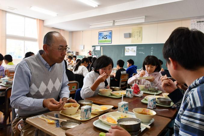 二子さといも入りのカレーを味わいながら生産者と交流する児童たち