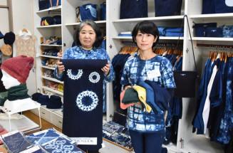 花巻絞りをあしらった布地を手にする滝浦敬子副社長(左)。創業110周年の節目に確かな技術をPRする