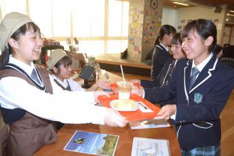 そろいのエプロンと帽子で、笑顔で接客する生徒(左側)=10月9日、福島県広野町・ふたば未来学園