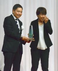 特別賞を受賞した日テレの岩清水梓。左は日本女子サッカーリーグの岩上和道理事長=4日、東京都内